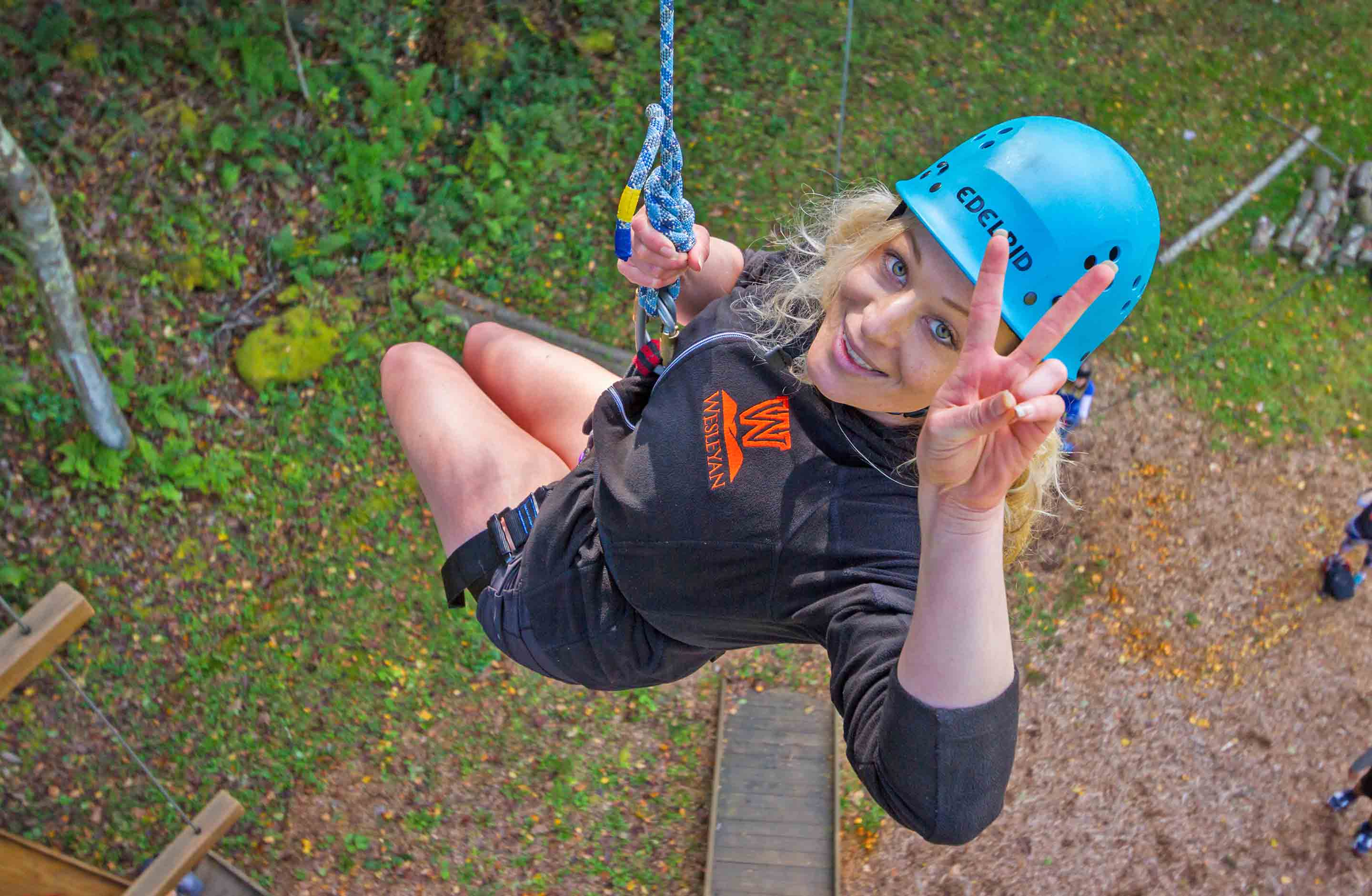 A college student flashes a peace sign while suspended in the air over the Team Challenge Course at ACE Adventure Resort