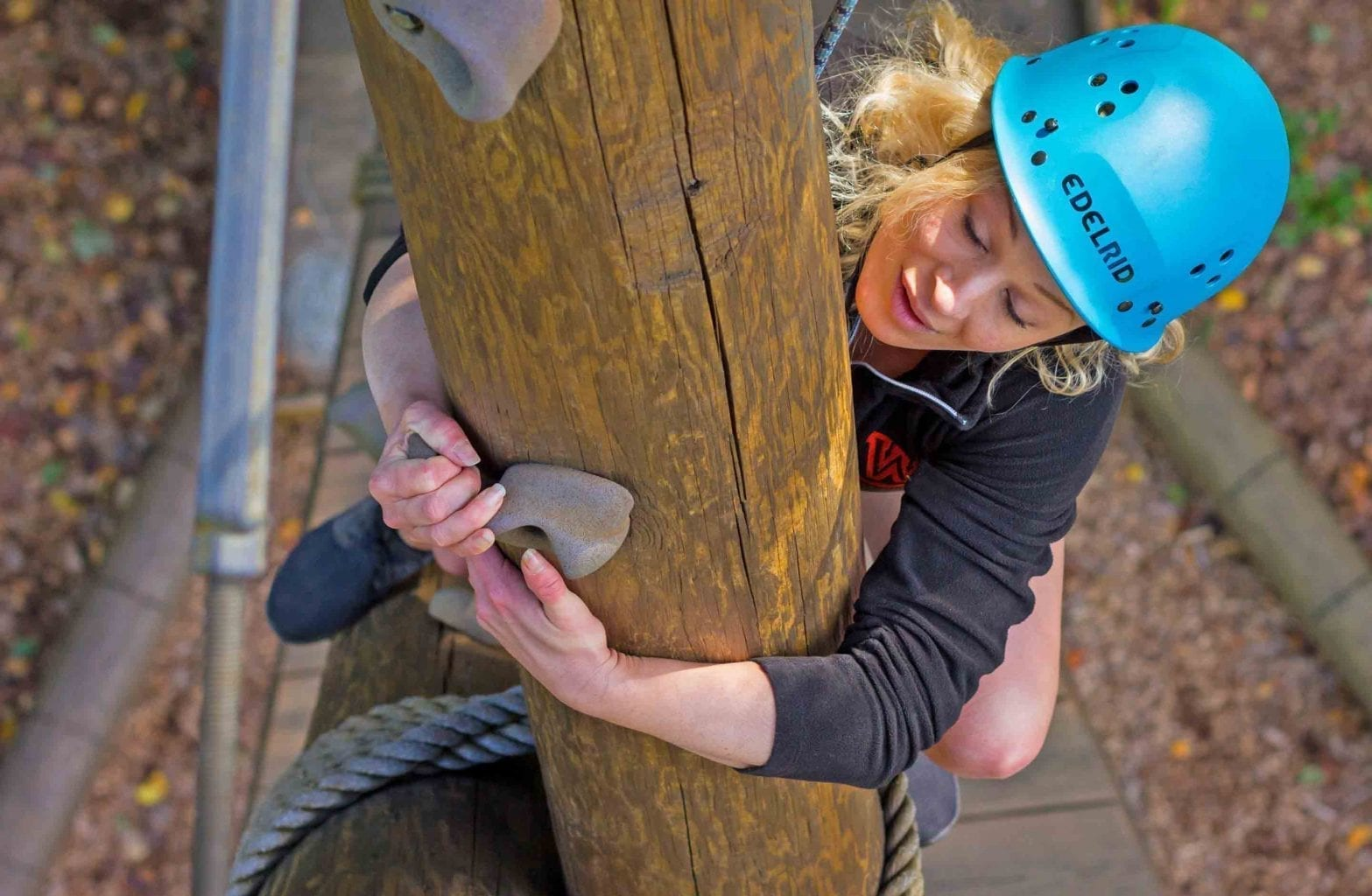 A woman climbs up the alpine tower with her college group on the Team Challenge Course at ACE Adventure Resort.