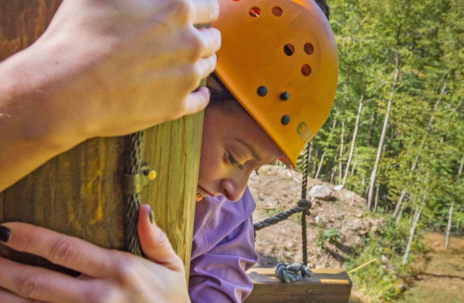 A girl holds onto the wooden climbing tower on the Team Challenge Course on a half day trip with ACE Adventure Resort.