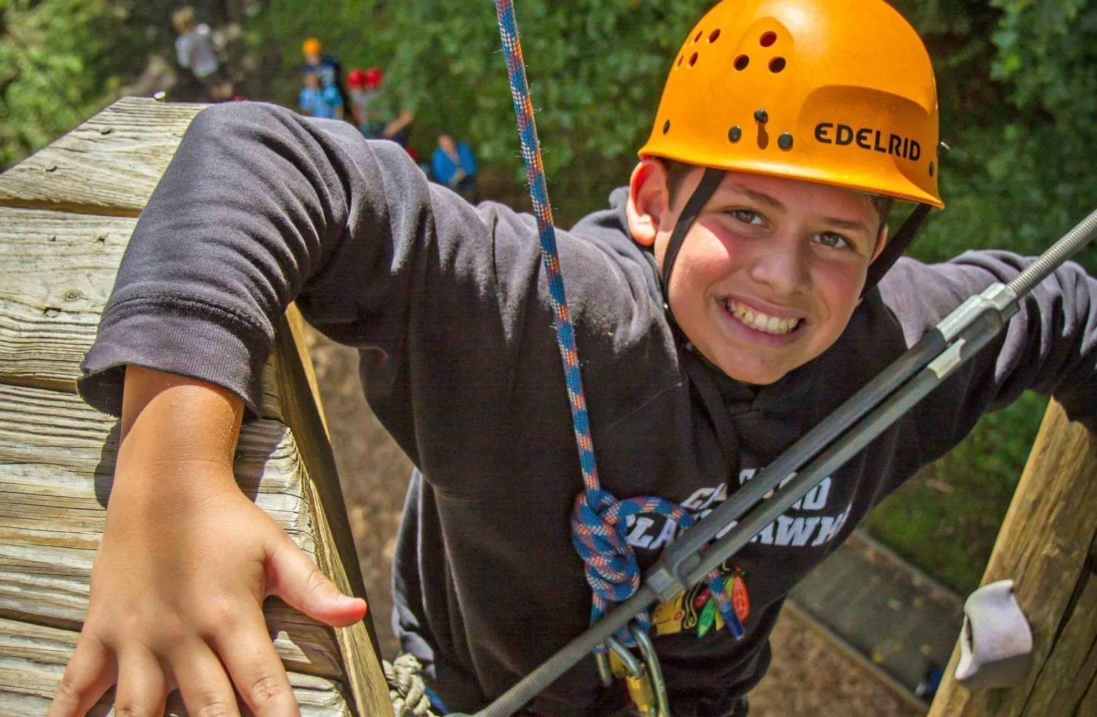 A kid smiles and makes his way up the climbing tower on the Team Challenge Course at ACE Adventure Resort in Southern West Virginia.