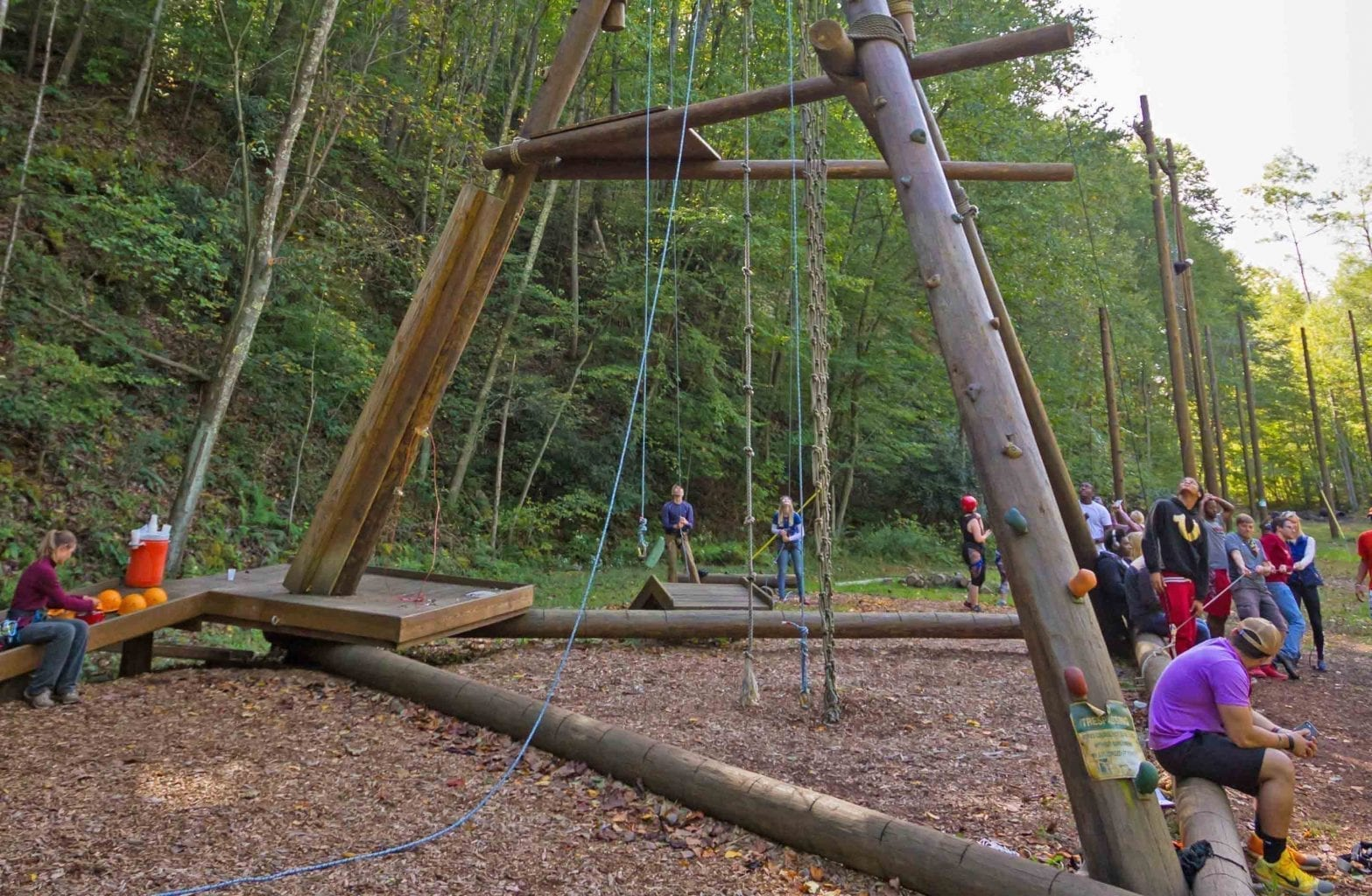 The view from the ground of the alpine tower with ropes and a group preparing to climb the Team Challenge Course at ACE Adventure Resort