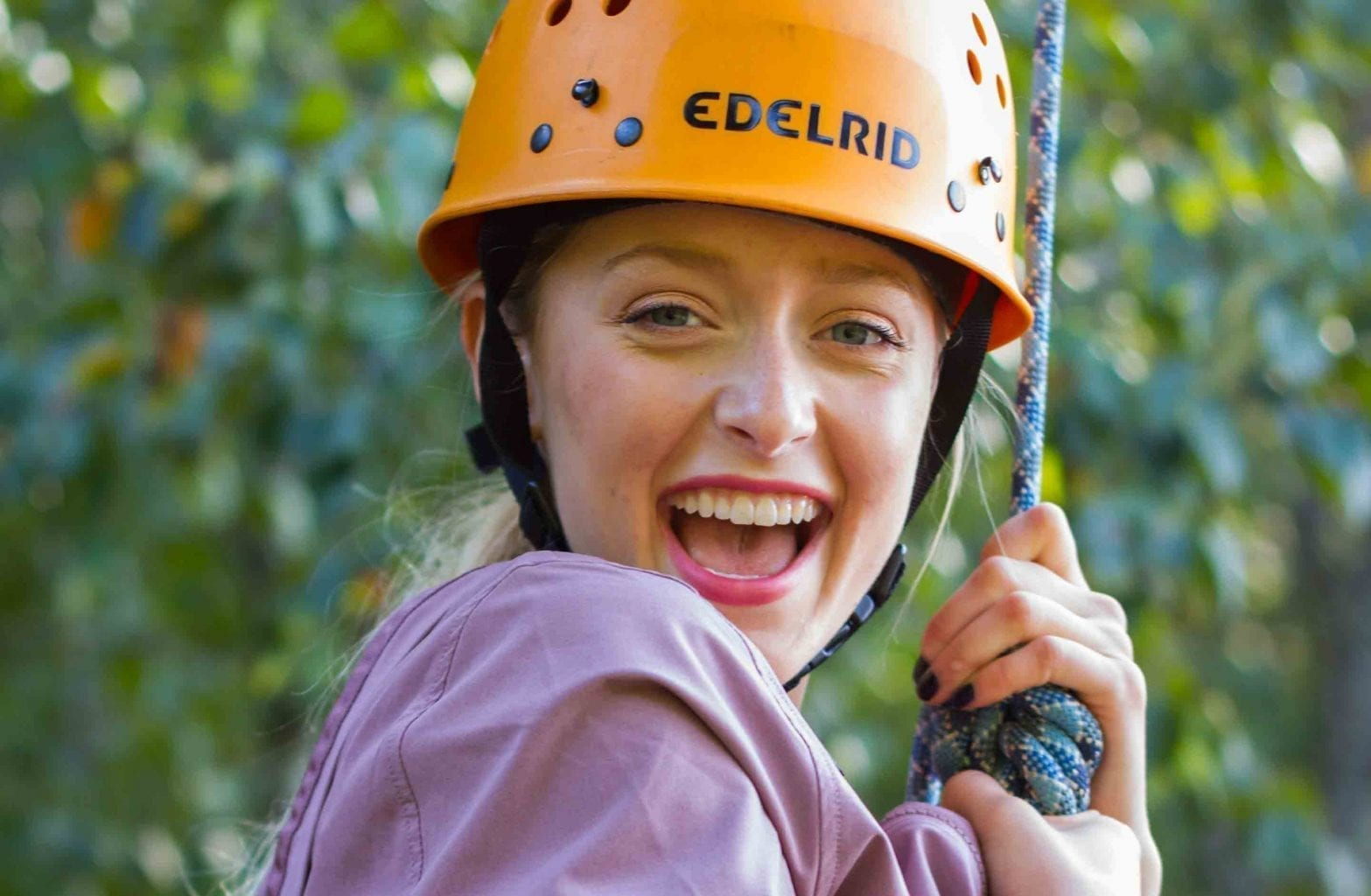 A girl smiles while harnessed into the rope climbing system on the Team Challenge Course at ACE Adventure Resort.