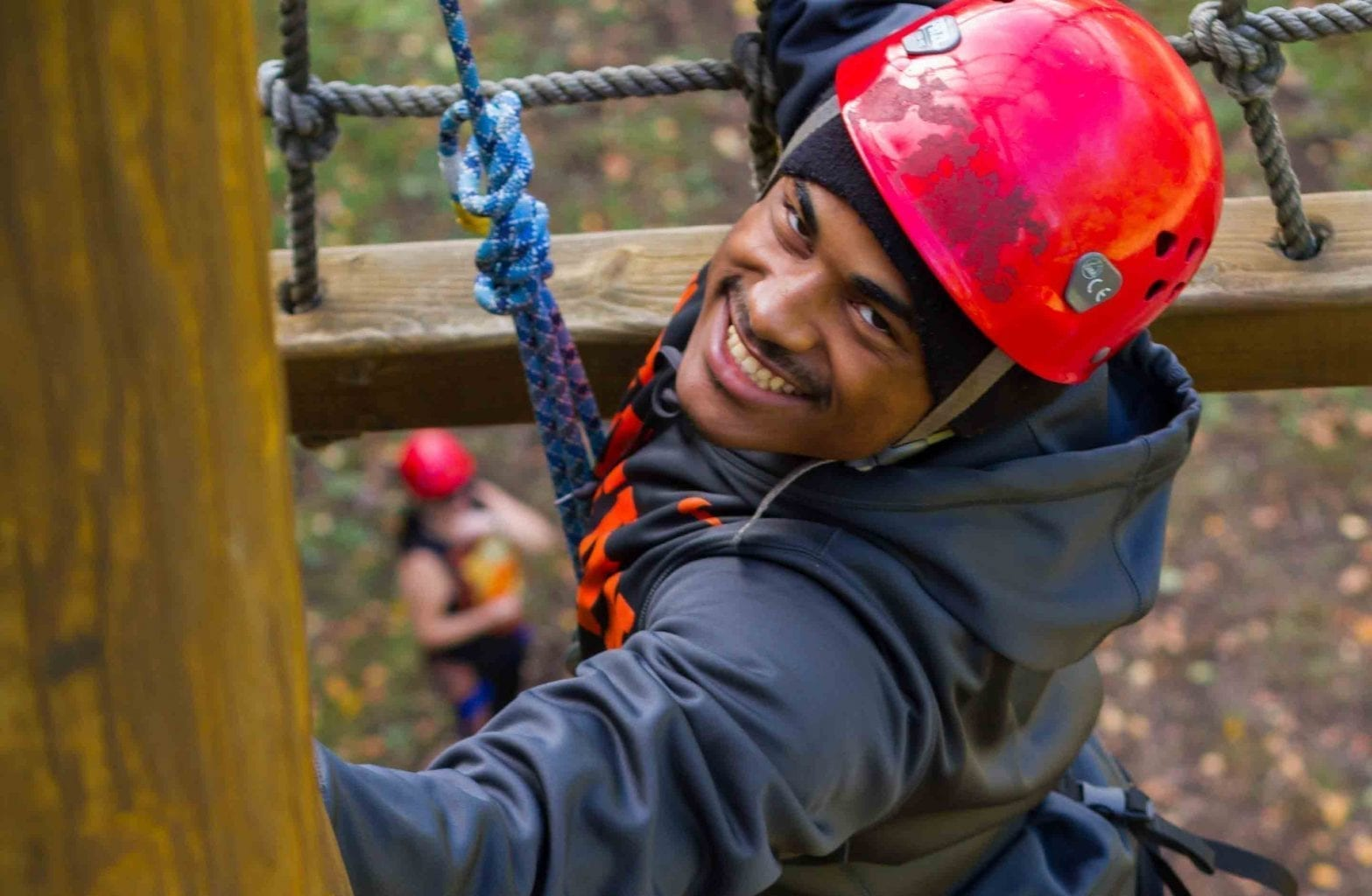 A college student on a group trip with ACE Adventure Resort ascends the ropes on the Team Challenge Course.