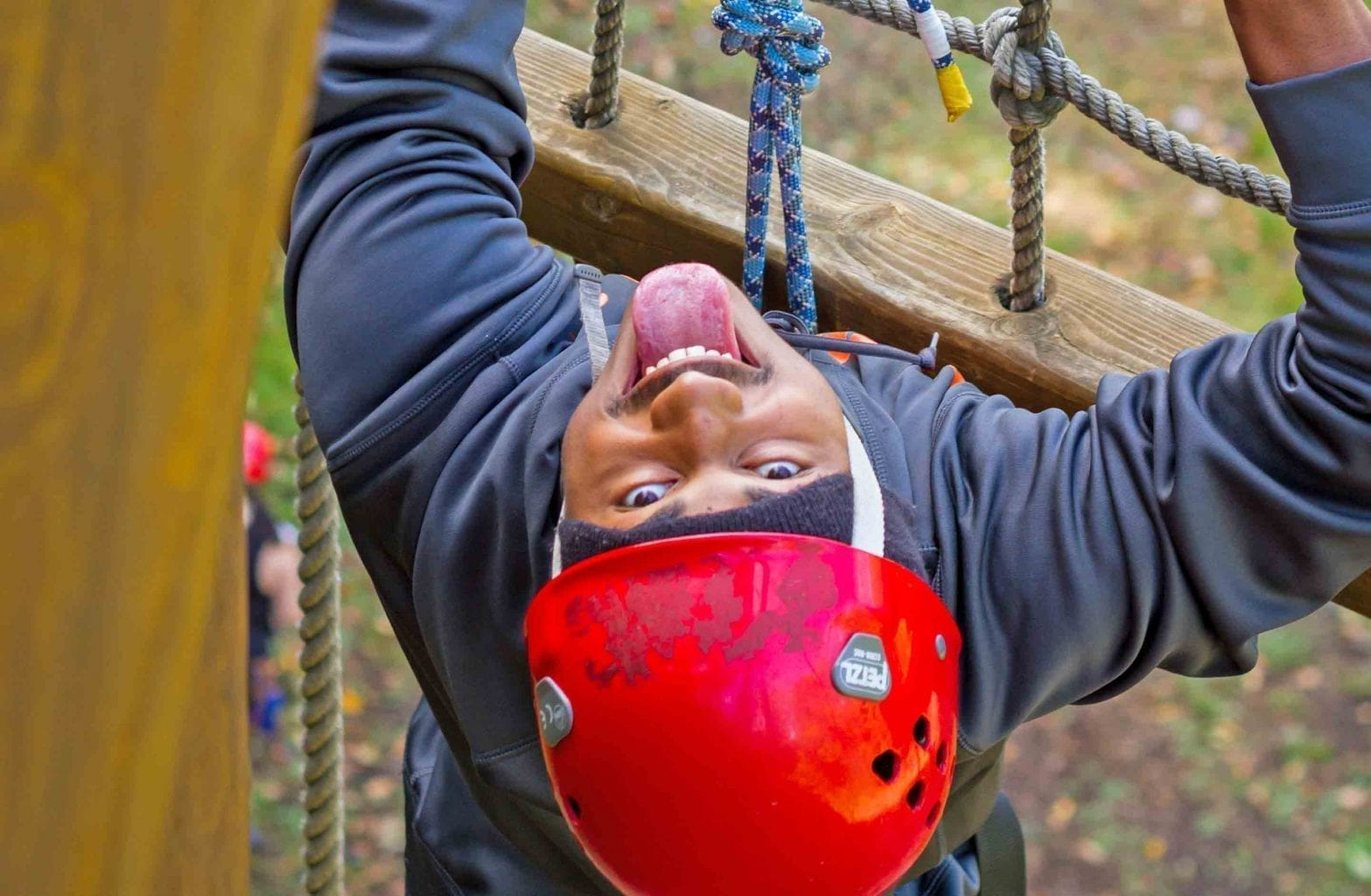 A student looks up at the camera while hanging from the rope ladder on the Team Challenge Course at ACE Adventure Resort