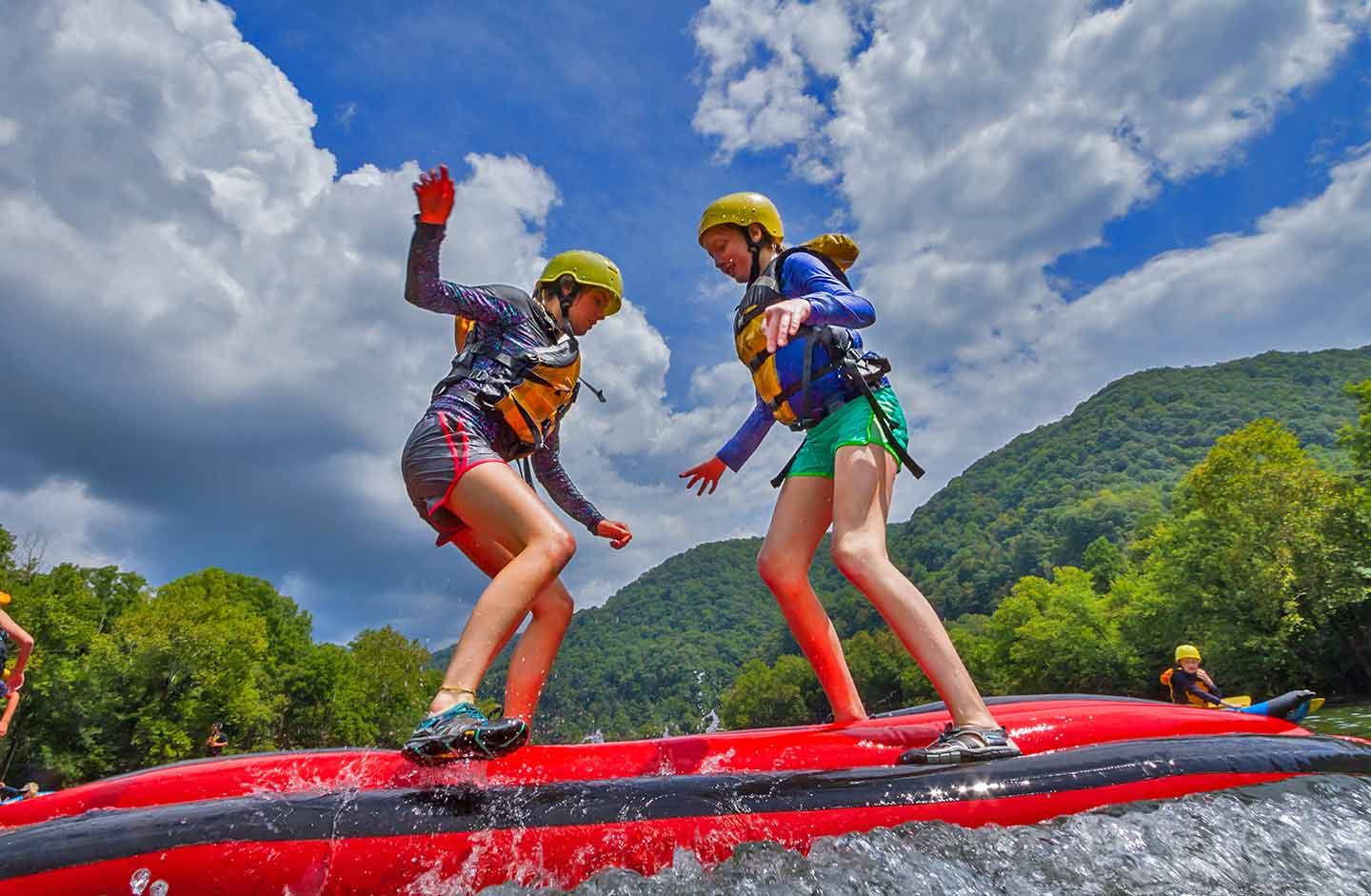Two young girls play on the upper new river a popular west virginia whitewater rafting kid-friendly rafting trip.