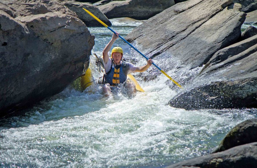 An ACE guest paddles the Summer Gauley rapids in an inflatable kayak.