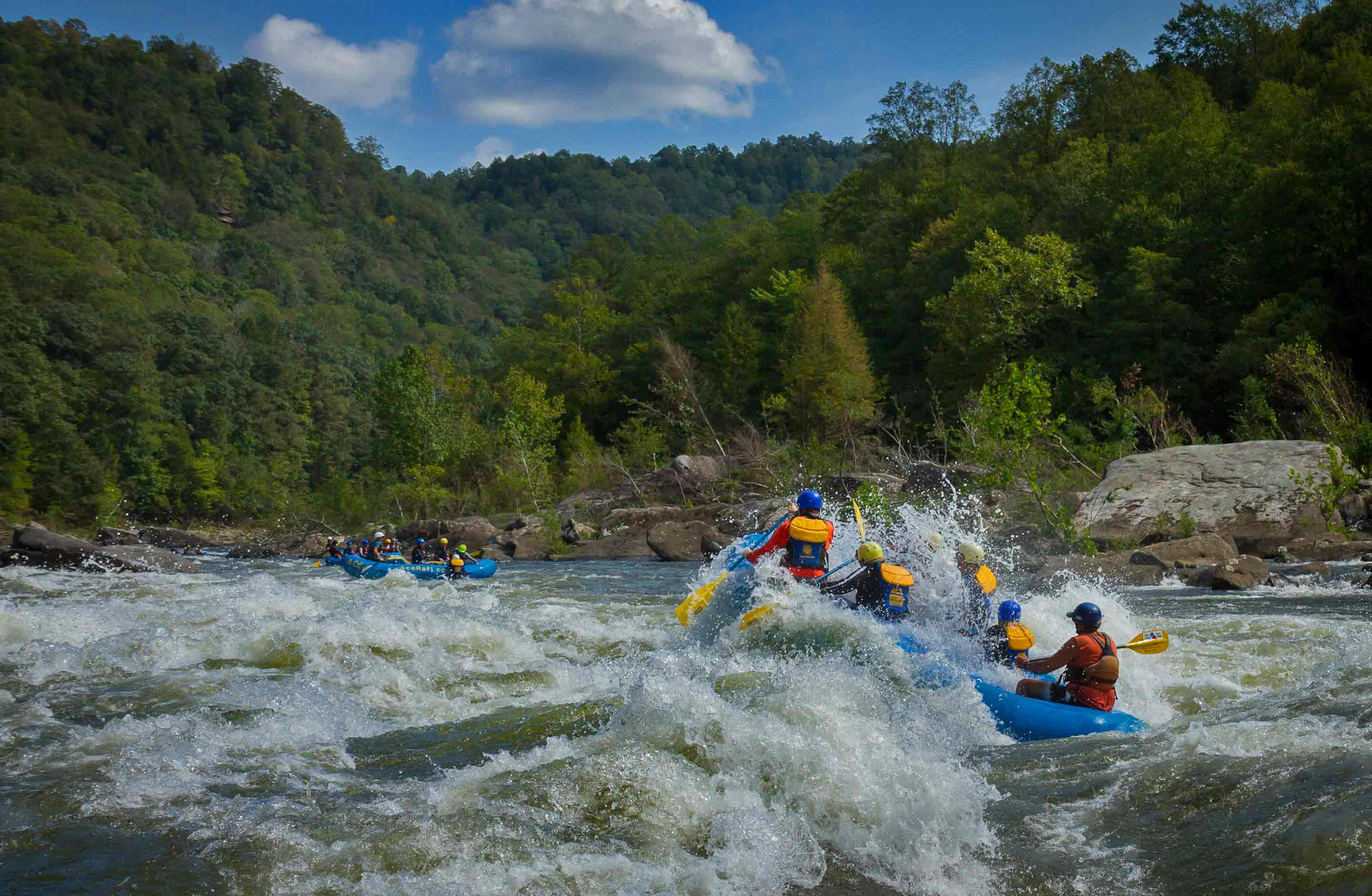 An ACE raft bursts through a wave on the Lower Gauley River whitewater rafting in West Virginia.