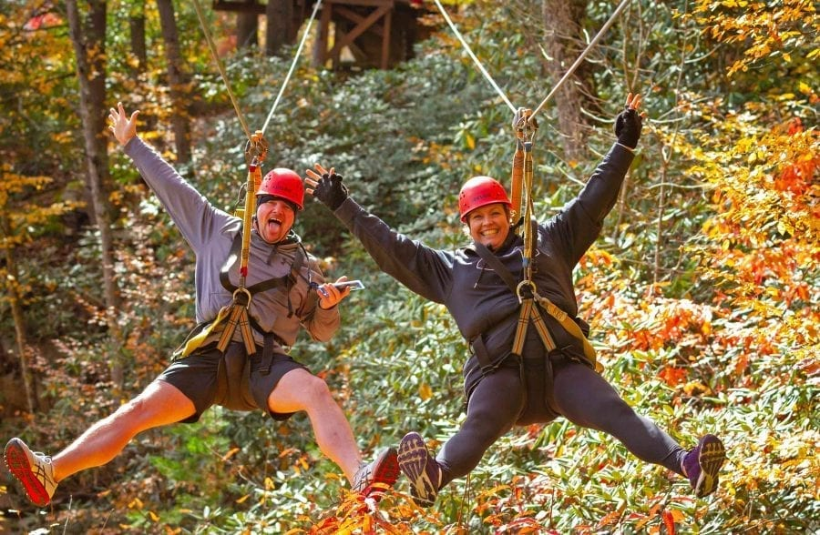 A couple zip lines together in the fall at ACE Adventure Resort in West Virginia.