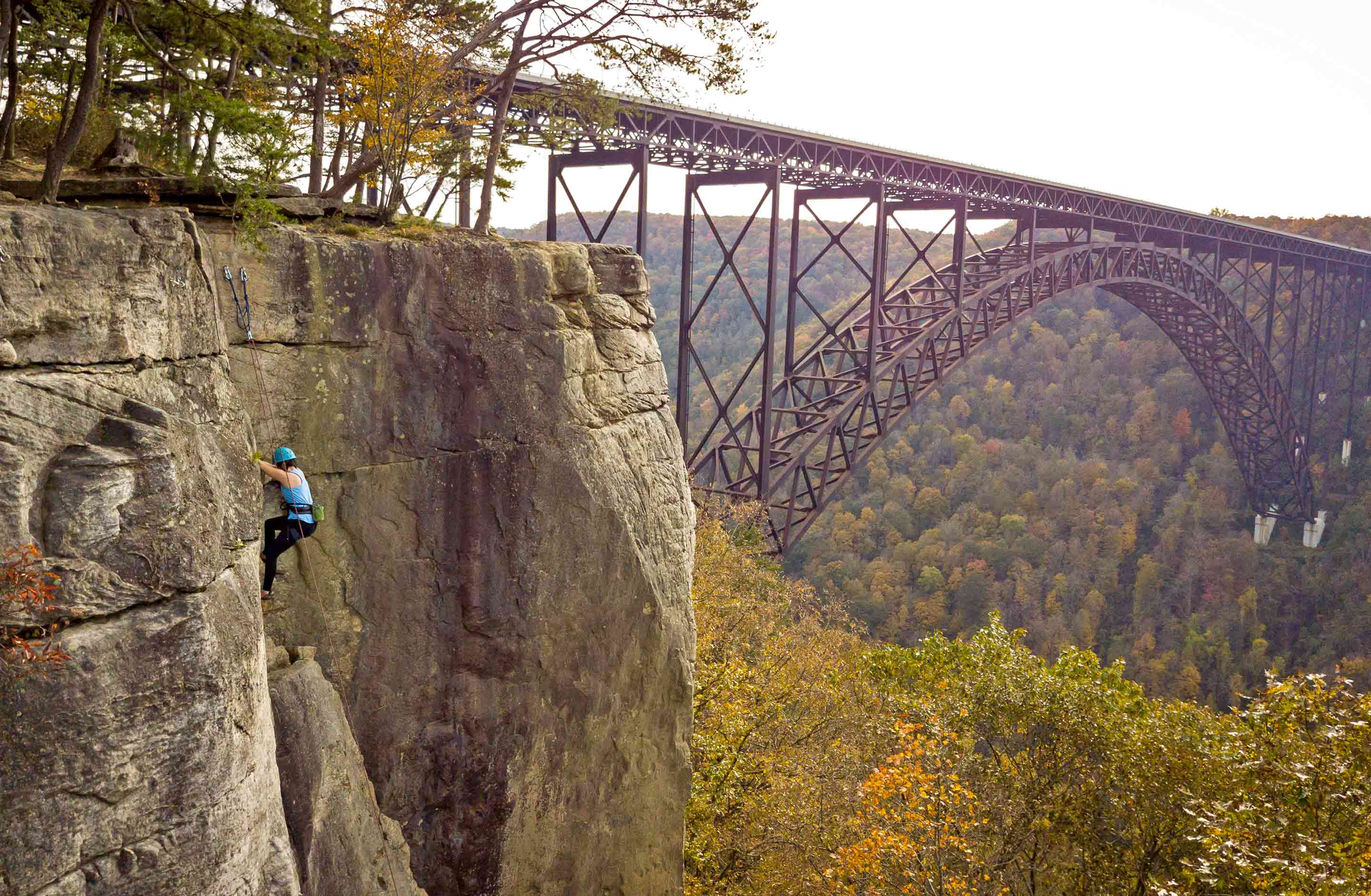 Climbing in the Lower New River Gorge with the New River Gorge Bridge in the background in West Virginia.