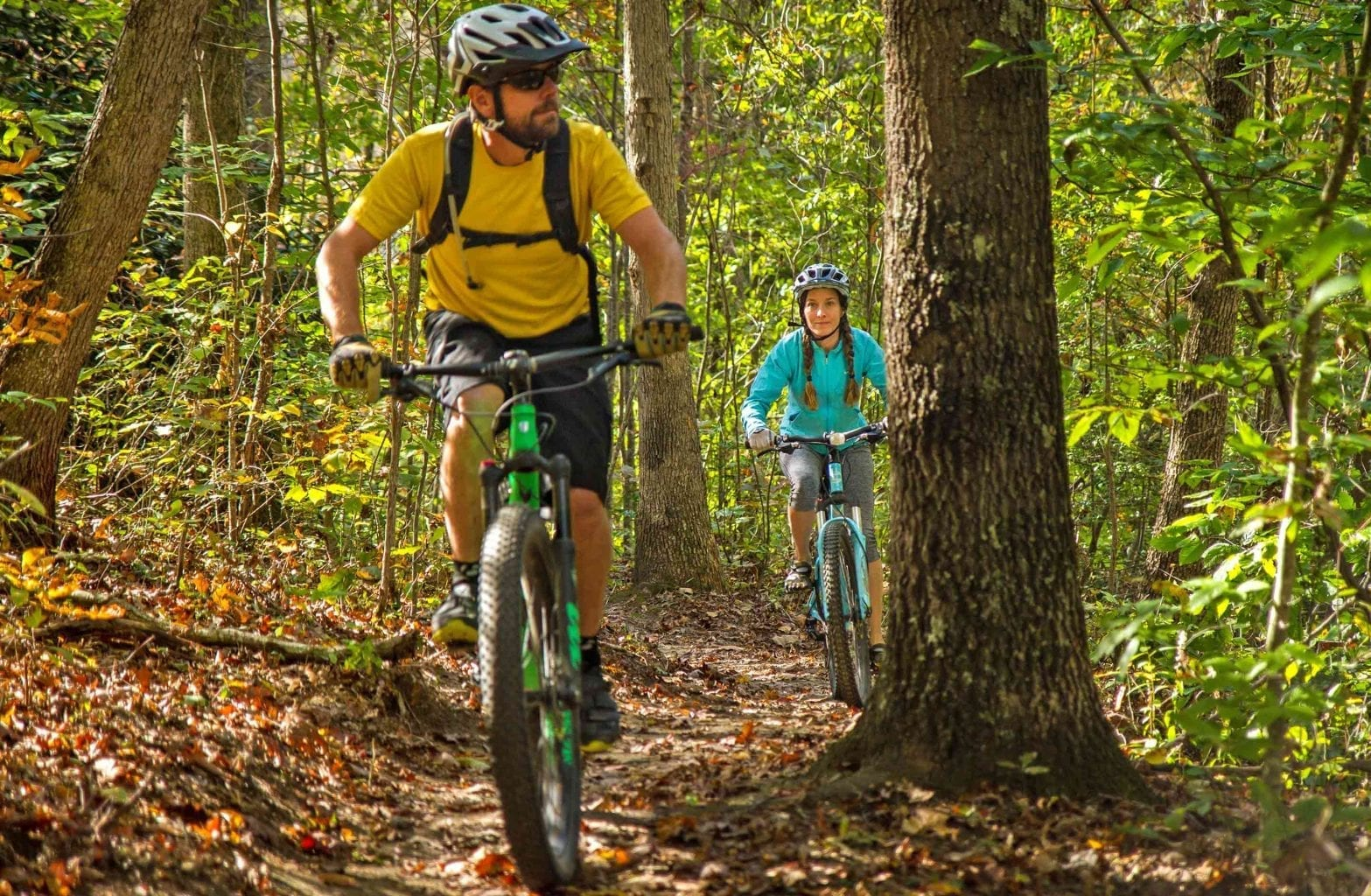 A couple goes mountain biking in the fall on New River Gorge trails with ACE Adventure Resort in West Virginia.
