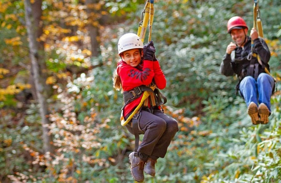 A father and daughter zip line together in tandem on the fall zip line course at ACE Adventure Resort in the New River Gorge.