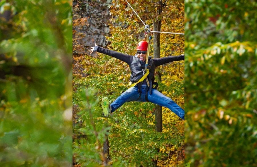 A woman strikes a pose on the zip line course at ACE Adventure Resort in West Virginia.