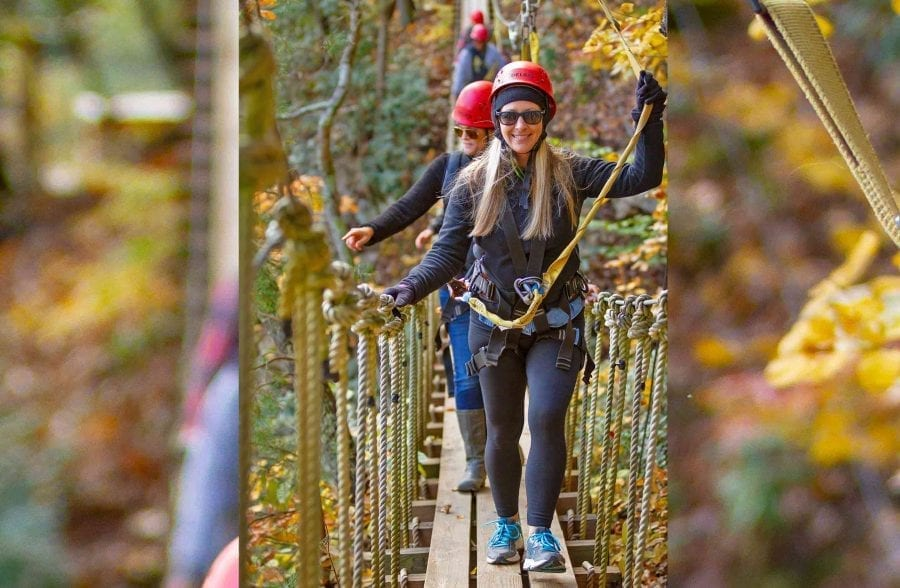 A group crosses the swinging rope bridge in the tree tops at the fall zip line course at ACE Adventure Resort in the New River Gorge, WV.
