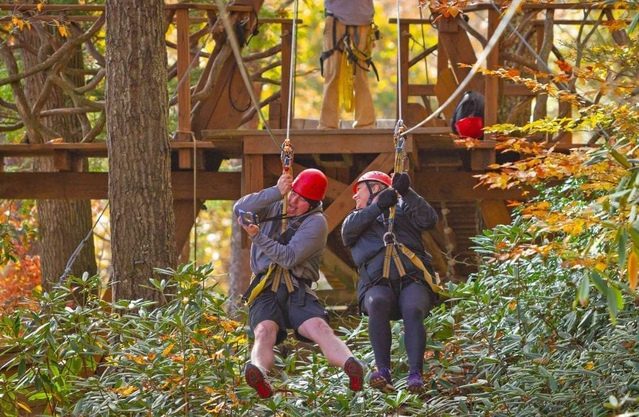A couple rides the zip line together on an adventure activity date with ACE in the New River Gorge, West Virginia.