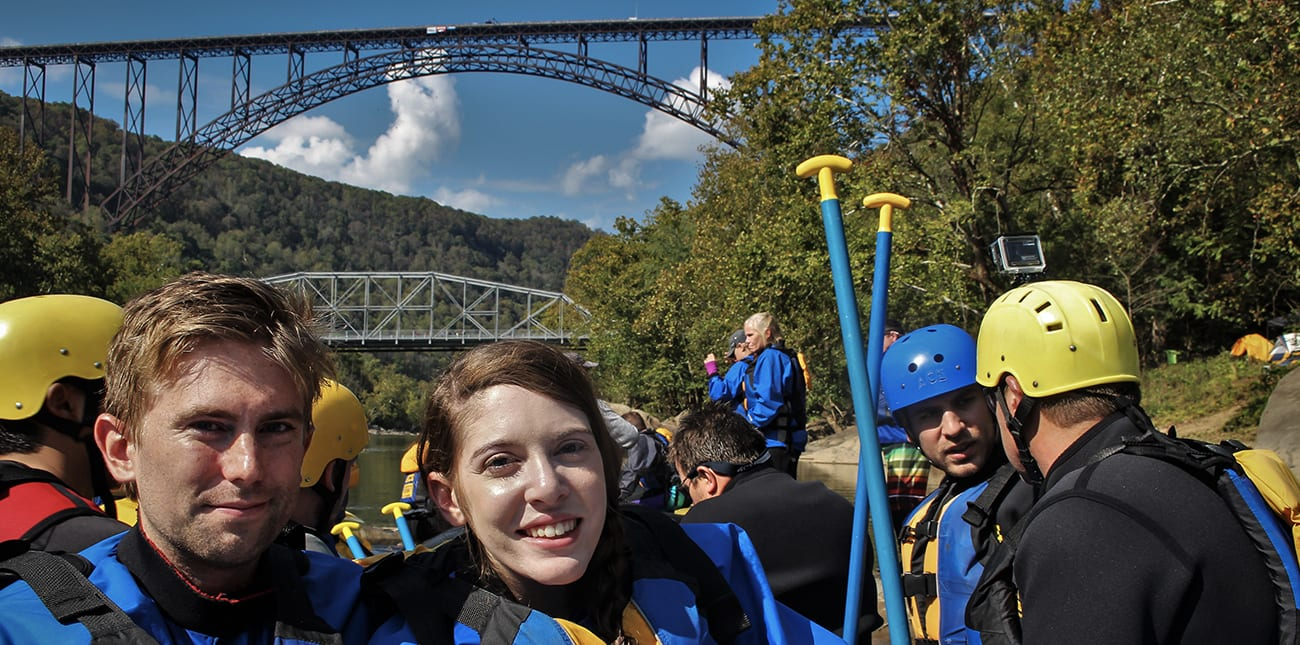 A couple on a Lower New River rafting trip poses under the New River Bridge on Bridge Day.