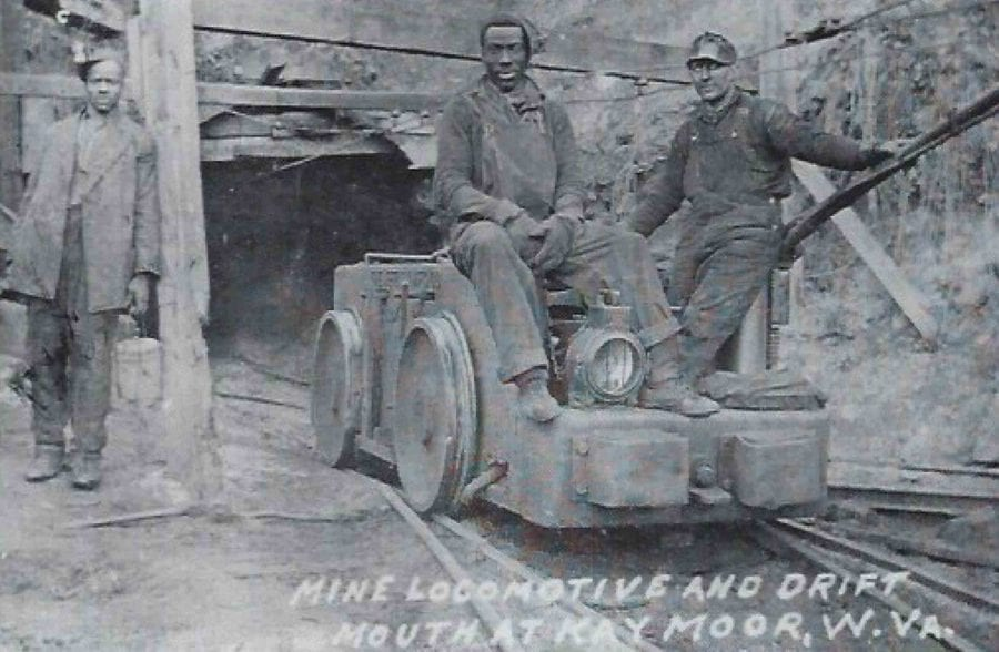 Coal miners pose on a mining rail car in front of Kaymoor mine entrance in the New River Gorge.