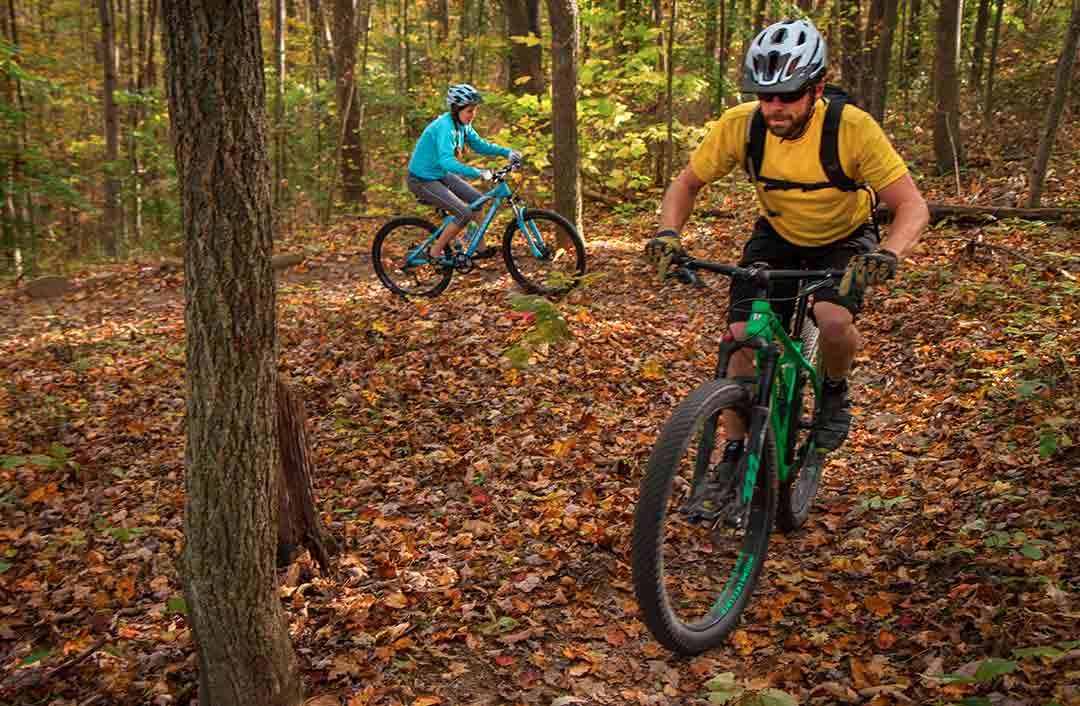 A couple enjoys a mountain biking ride through the woods at ace, the perfect romantic getaway for outdoor lovers.