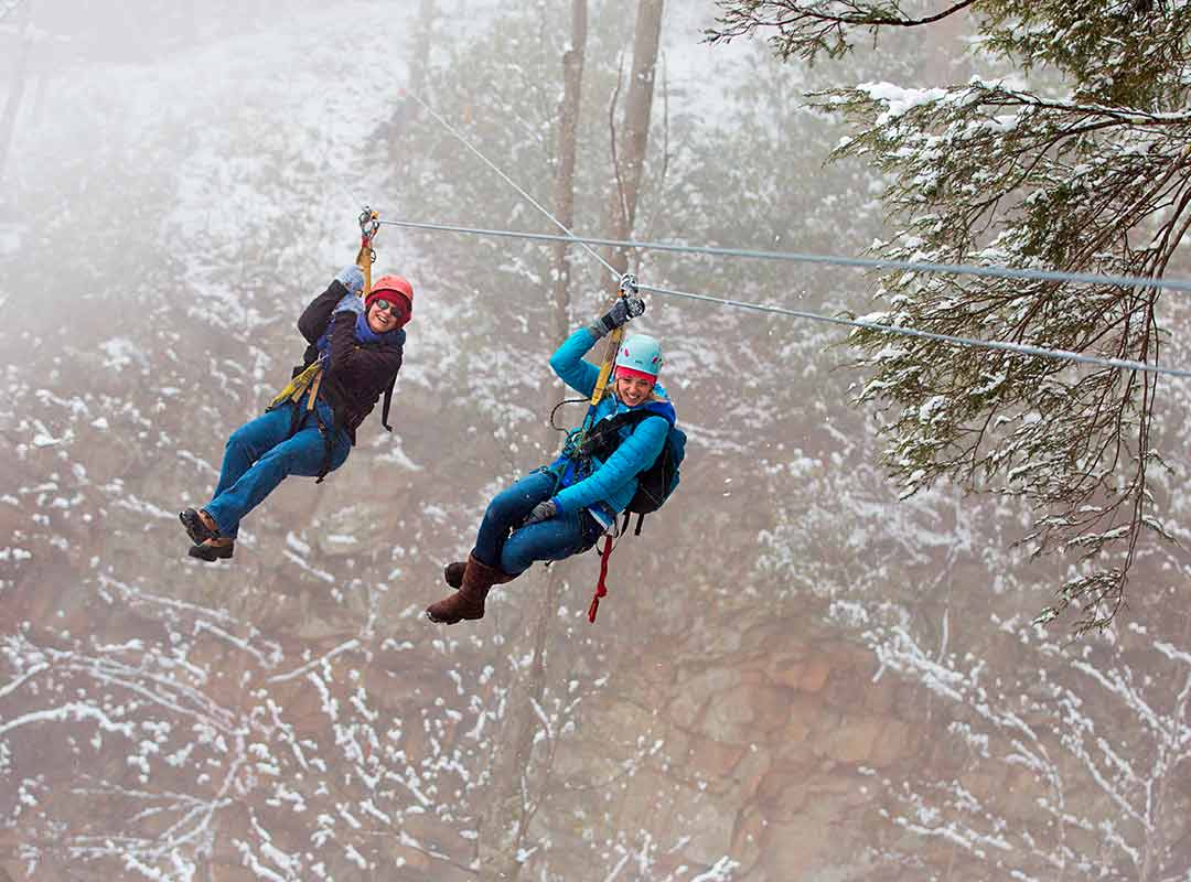 Two women fly through the trees of the New River Gorge winter at ACE Adventure Resort.