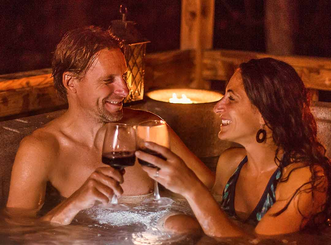 A couple enjoys a cabin hot tub at ACE during the winter in West Virginia.