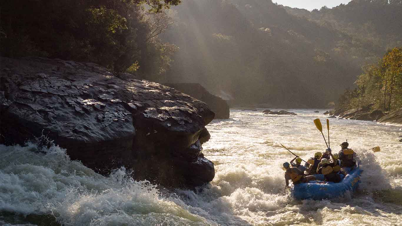 Photo of guests rafting the Upper Gauley with sun shining in the background