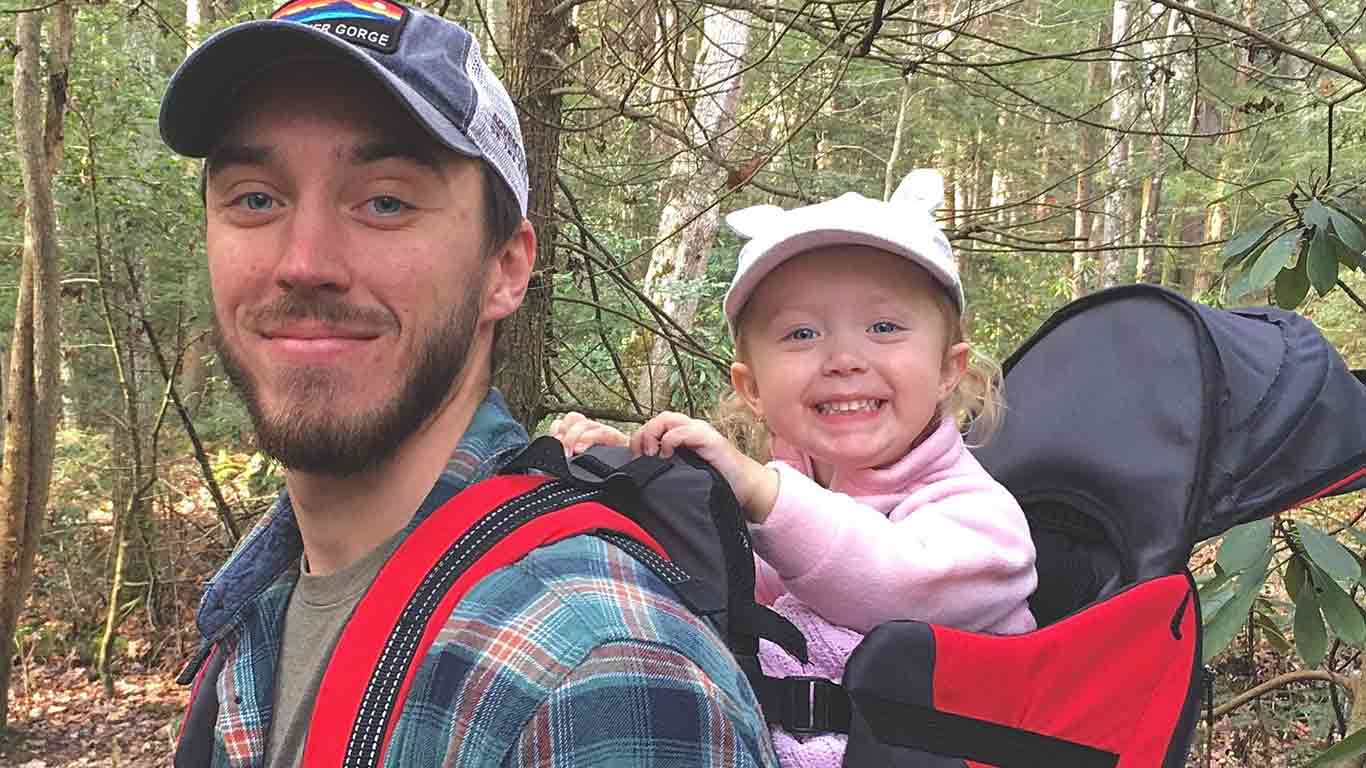 Jake posing with his daughter on a trail