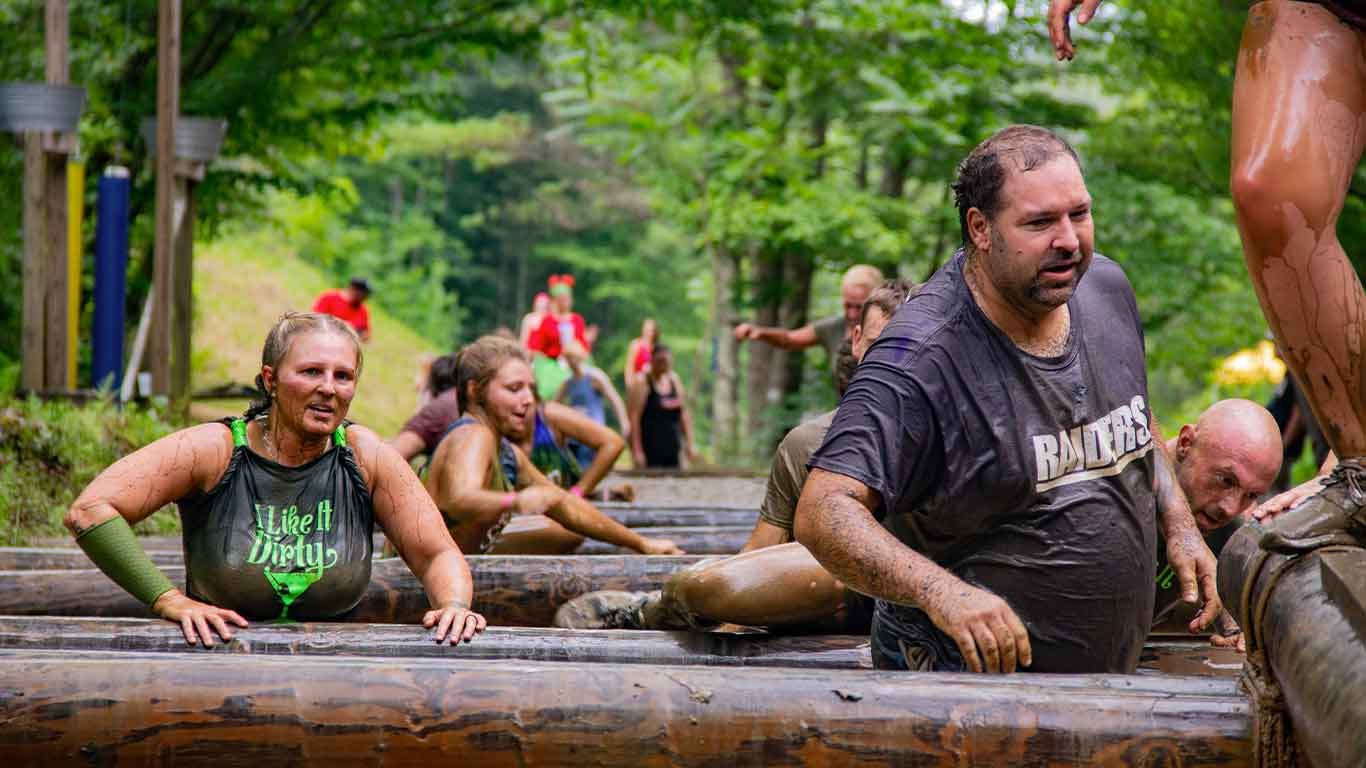 Racers on the obstacles on the mud run